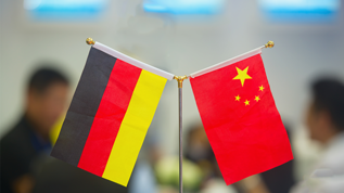 A german and a chinese flag on a table.